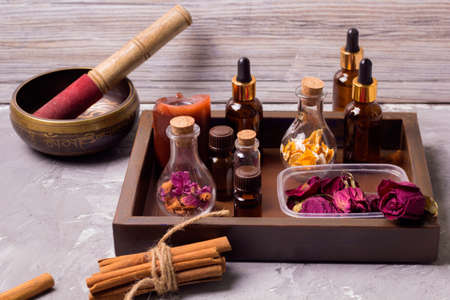 tibetan singing bowl spa set bottles on a vintage wooden tray: dry rose petals,orenge peel,aroma oils,sea salt,cinnamon