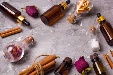 frame with spa set bottles on a vintage wooden tray: dry rose petals,orenge peel,aroma oils,sea salt,cinnamon, copy space
