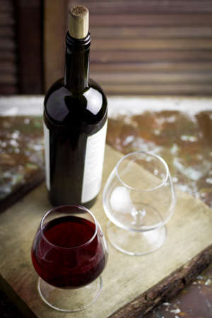 wine glass with expensive red wine,  blurred bottle of wine, wooden background 写真素材