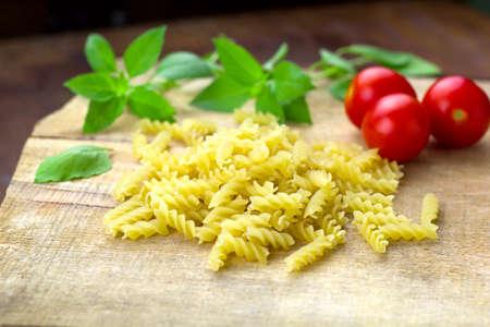 pasta,tomatoes,basil on a wooden cutting board Standard-Bild