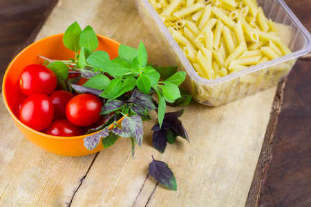 pasta,tomatoes and fresh basil leaves on a wooden cutting board