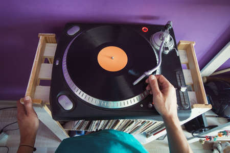 top view man puts a vinyl record in the player