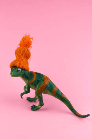 funny green dinosaur toy in little knitted orange hat  near on pastel pink background 写真素材