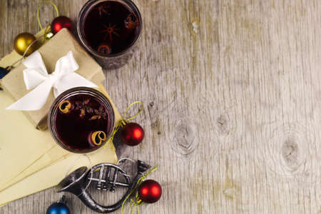 mulled wine, christmas balls, gift box on wooden rustic background copy space