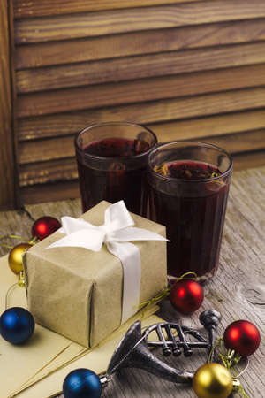 mulled wine, christmas balls, gift box on wooden rustic background