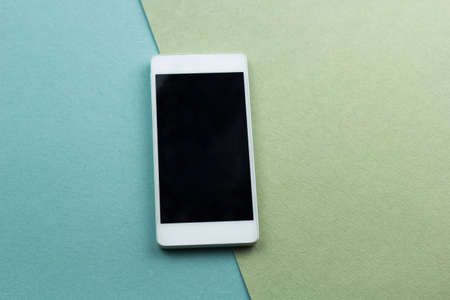 top view smartphone flat lay on a green and blue background
