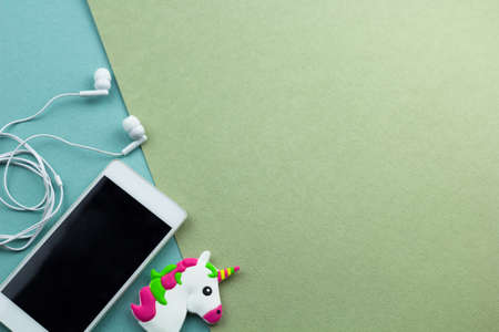 top view smartphone with earphones  and little unicorn toy head flat lay on a green and blue background