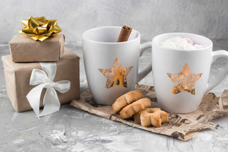 winter hot sweet drink cups with gift boxes and cookies on a shabby gray concrete background Stock Photo