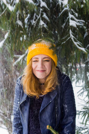 cute happy woman in yellow hat under snow fall in winter forest