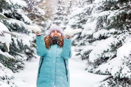 young happy excited woman in knitted hat and blue down jacket throws snow in spruce forest, winter happy portrait, holiday Christmas vibes