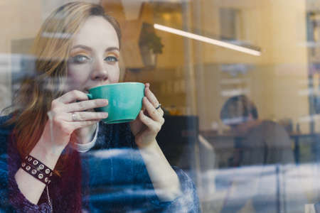 woman in a coffee shop, shot through the glass Stock Photo
