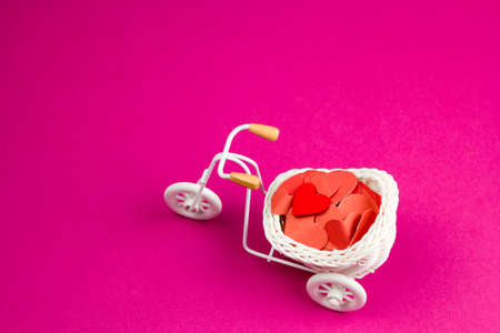 cute trinket retro bike with white wicker basket full of red paper hearts Фото со стока