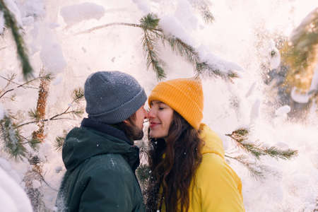 young beautiful man and woman standing close to each other under fallen snow , spend winter holidays together  concept Banque d'images