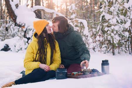 ute couple drinks tea  in a winter forest 版權商用圖片