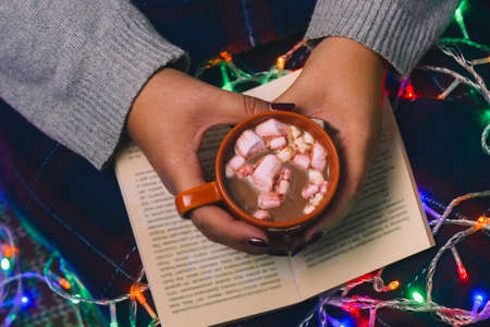 woman with book and hot drink in hands top view,cozy winter holidays