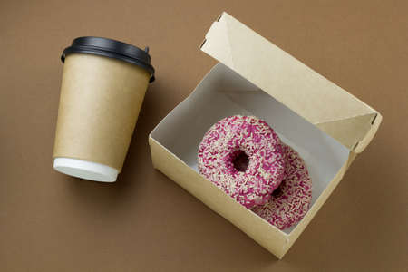 top view disposable paper cup with plastic lid and cardboard box with donuts on brown background