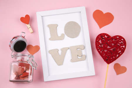 top view white frame with letters L O V E  , red heart  and jar with  hearts on a pastel pink background Reklamní fotografie