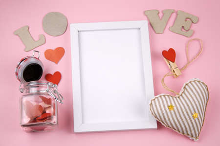 top view white frame with letters L O V E  ,  heart  and jar with  hearts on a pastel pink background Banco de Imagens