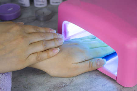 close up of womens hand and nail polish drying lamp, manicure process in beauty salon