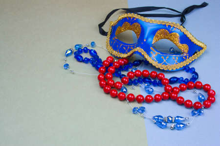 blue carnival mask and beads on green and blue background