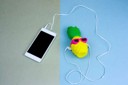 top view flat lay cute pineapple in sunglasses and smartphone on a green and blue background, summer clothing set women's fashion