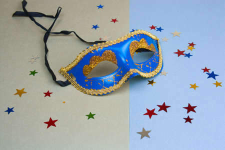 blue carnival mask and star glitters on green and blue background