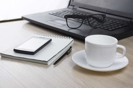 workplace with  laptop, notebook, glasses and a mug of coffee selective focus