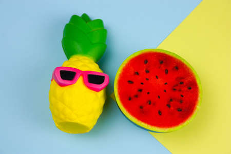 top view summer vibrant blue and yellow  background with funny pineapple toy in sunglasses and squishy toy watermelon