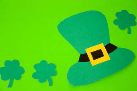 St Patricks Day paper shamrocks and paper hat over green background