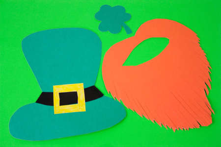 St Patricks Day  paper shamrocks,paper red beard  and paper hat over  green background