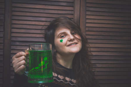 young woman with a mug of green ale in a bar opposite a wooden wall