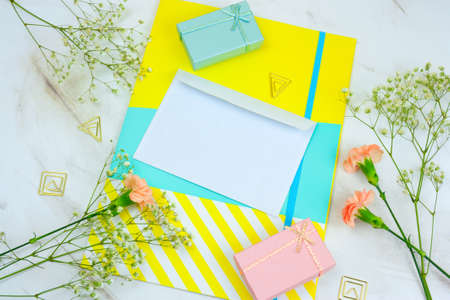 top view blank white envelope, gift boxes ,bright folder and flowers on a marble table