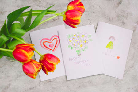 beautiful tulips and handmade card with kid's drawing  for Mother's Day on marble background, top view