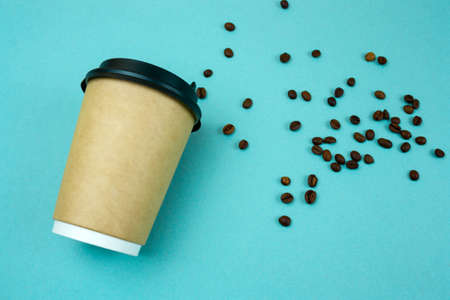 top view paper coffee to go cup  coffee beans on blue  background