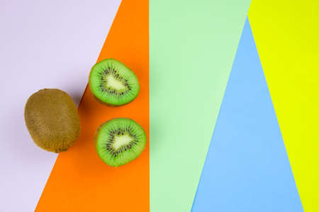 top view kiwi fruit on a vibrant multicolored stripped background Banco de Imagens