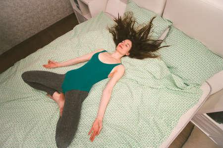 Vista superior hermosa mujer joven acostada en la cama, shavasana, yoga matutino en la cama, concepto de belleza y estilo de vida saludable Foto de archivo