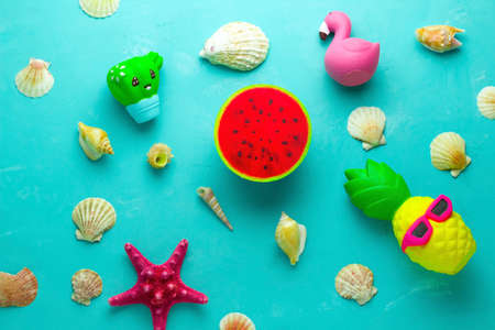 top view flat lay seashells, flamingo, pineapple, watermelon,cactus, starfish on blue background, summer travel background