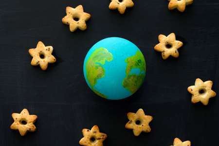 top view  handmade model  of Earth planet  and cookies in the shape of stars on the chalkboard , space and astronomy concept
