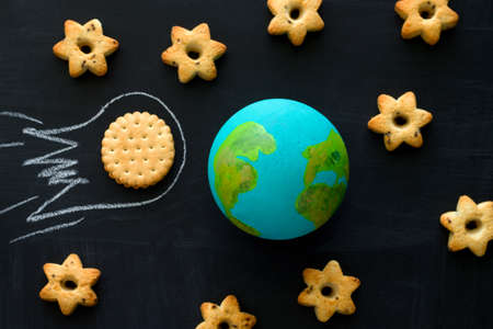 top view handmade model of Earth planet, cookie meteorite and cookies in the shape of stars on the chalkboard , space and astronomy concept