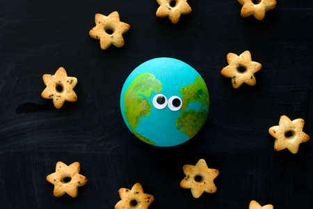 top view  handmade model  of Earth planet with funny googly eyes  and cookies in the shape of stars on the chalkboard , space and astronomy concept