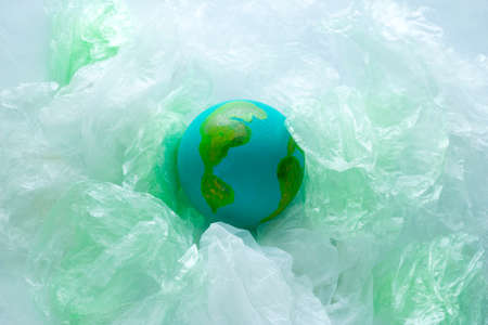 top view of a small model of the  Earth planet among plastic bags, environment, global pollution  concept, earth day Фото со стока