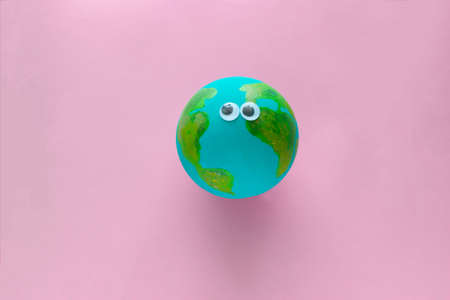 Earth planet model with googly eyes on a pastel pink background Stok Fotoğraf