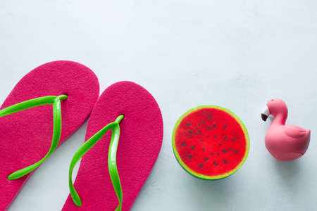 pink beach flip flops and squishy toy watermelon and flamingo on white background copy space