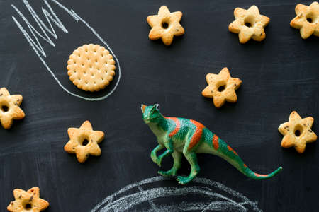 plastic dinosaur and cookies on the chalkboard, play and learning with the children,  dinosaurs became extinct because of a meteorite concept