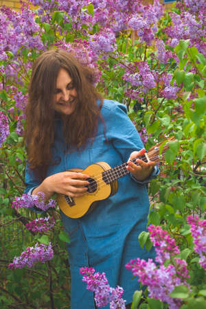 beautiful young girl with curly hair dressed in denim dress playing the ukulele on a background of blooming lilac Stock Photo