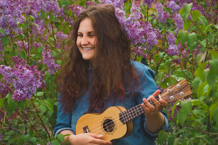portrait of beautiful young girl with curly hair   playing the ukulele on a background of blooming lilac