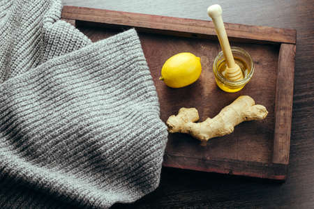 top view wooden tray with woolen scarf ,lemon,ginger, honey
