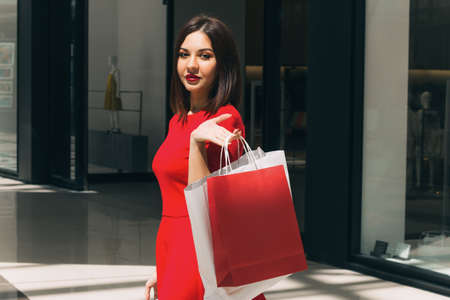 portrait of young beautiful brunette in red dress with shopping bags