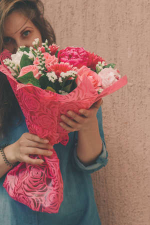happy young woman in denim dress with bouquet of gentle fresh flowers