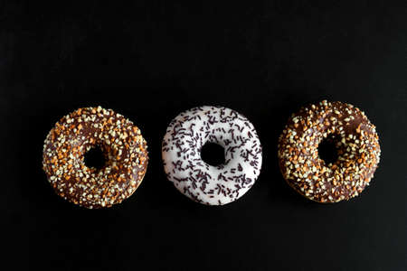 top view chocolate nad vanilla doughnuts on a black background